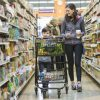 Woman walking by son carrying shopping cart at supermarket